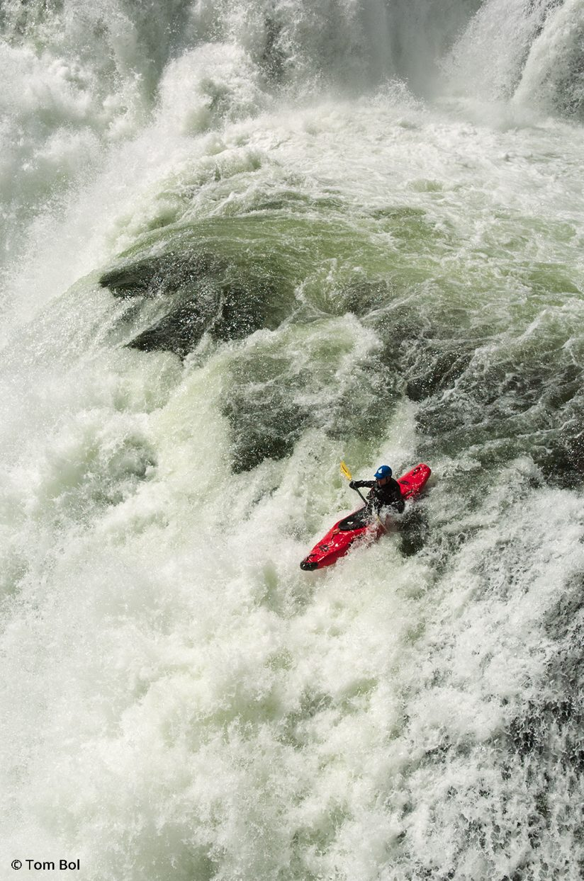 adventure sports photography, image of kayaker descending a waterfall