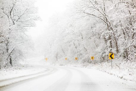 Winter landscape photography: snowy roadway with bright yellow curve signs