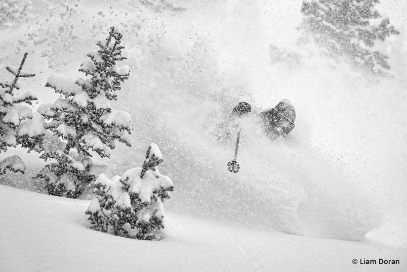 Black-and-white image of a skier emerging from a spray of powder.