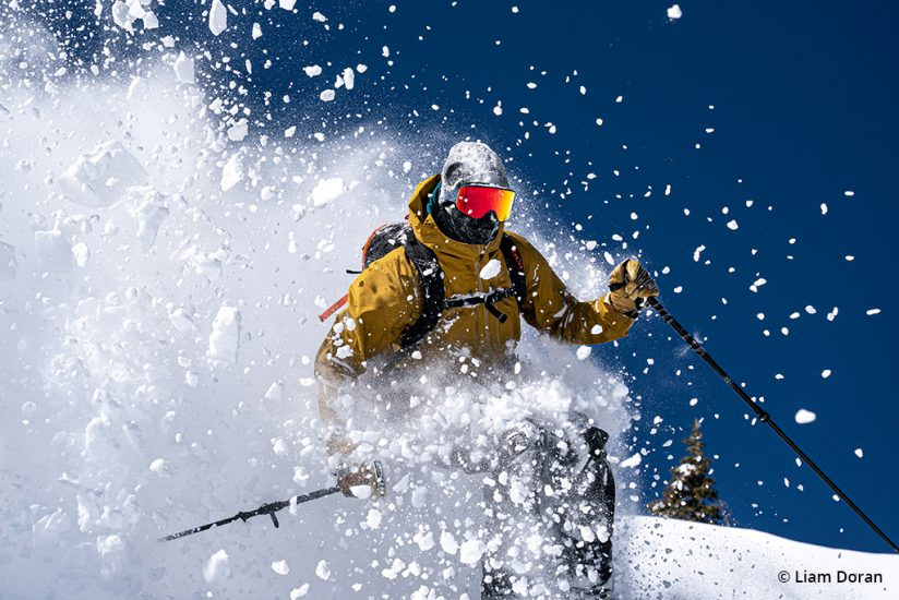 Image of a skier blasting through snow.