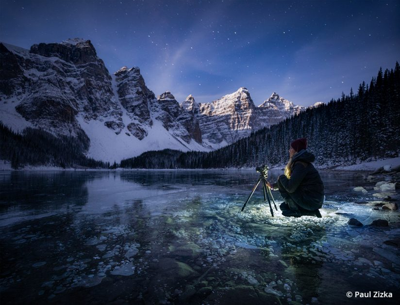 Image of a photographer taking photos at night on a frozen lake.