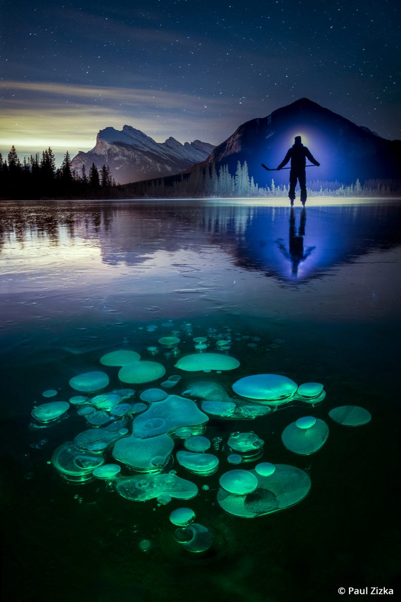 Image of frozen methane bubbles and ice skater silhouetted.