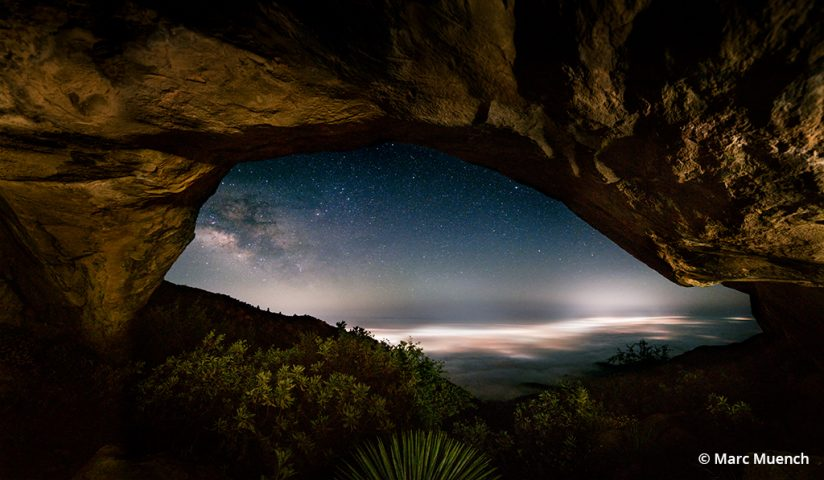 A photo looking through a cave to the starry sky beyond.