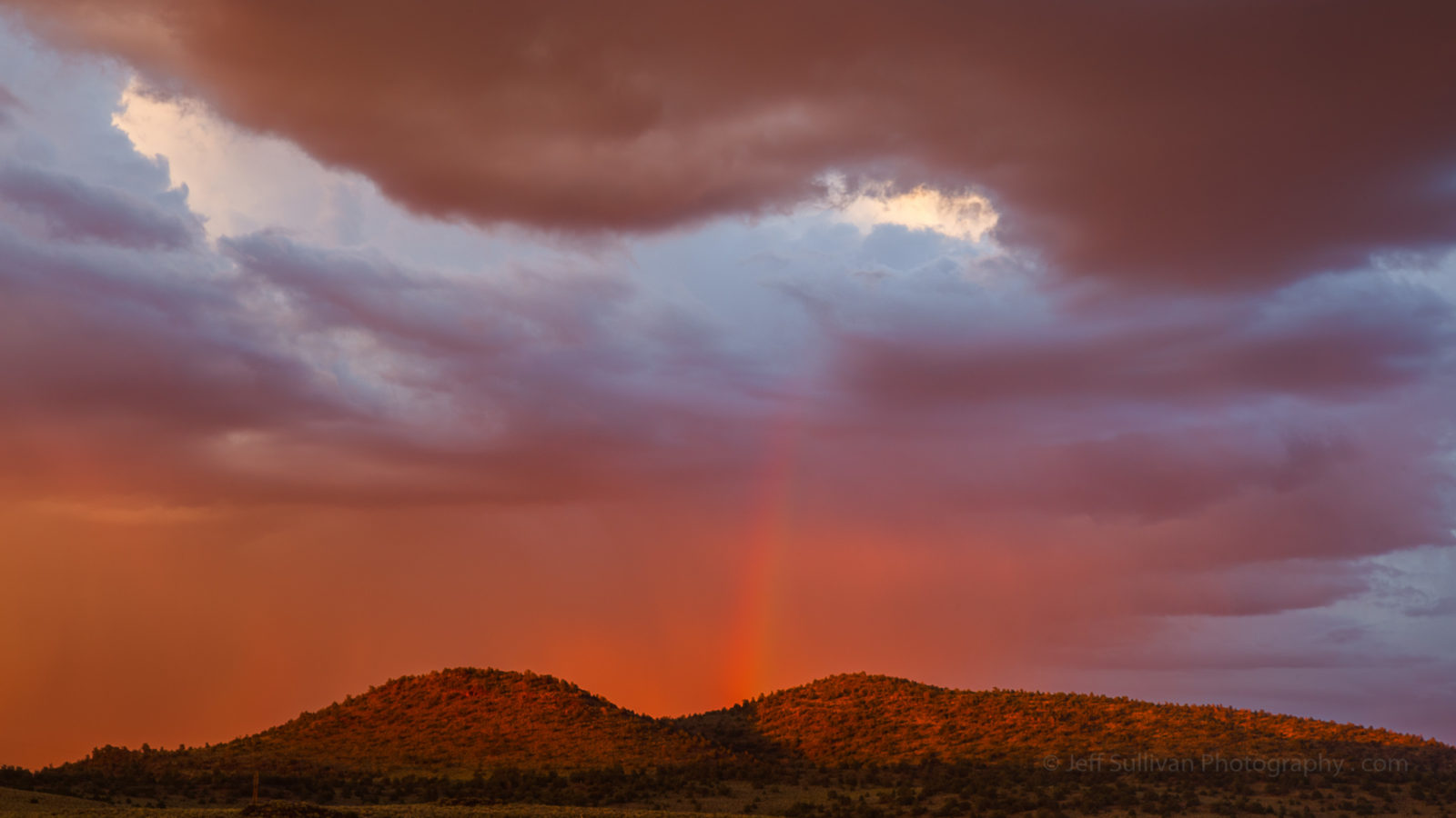 Sunset Rainbow Between Clouds and Hills