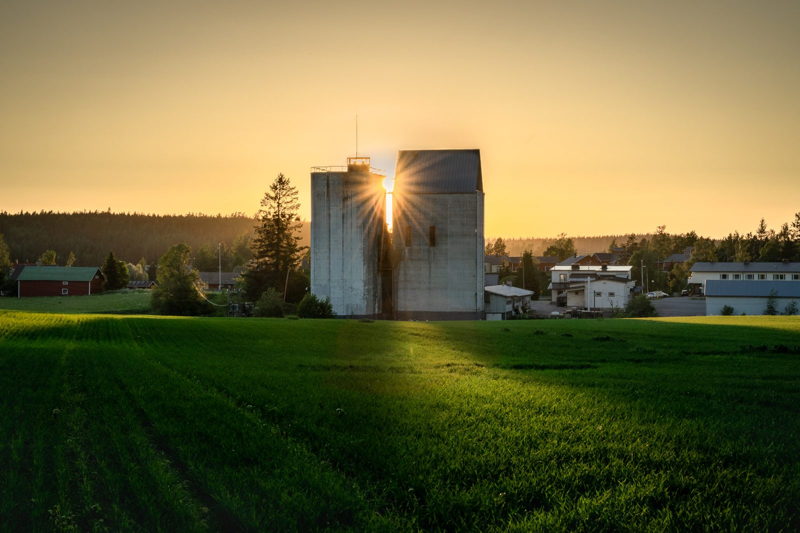 Sunsets behind a silo.
