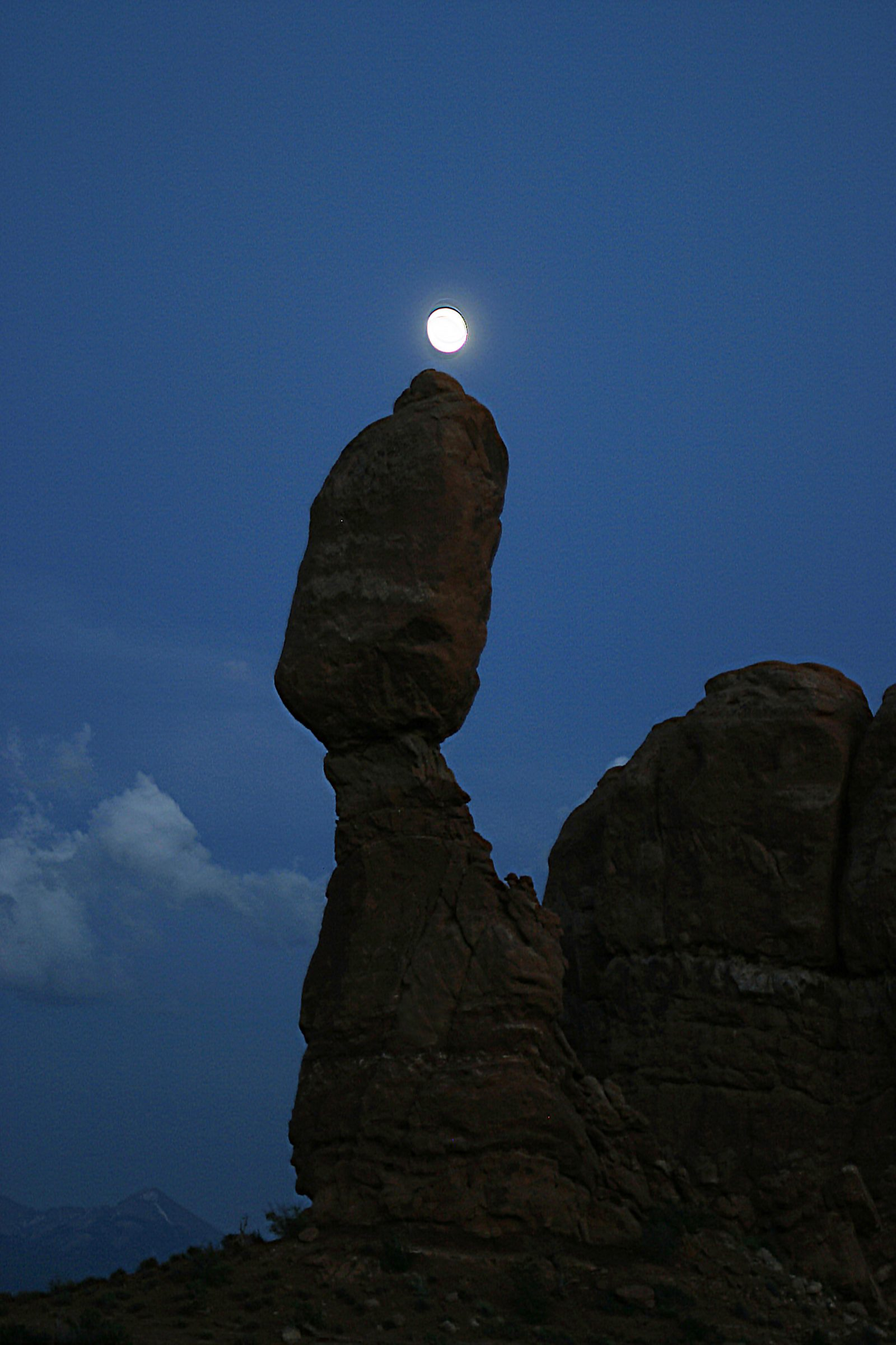 Moon sits upon balanced rock