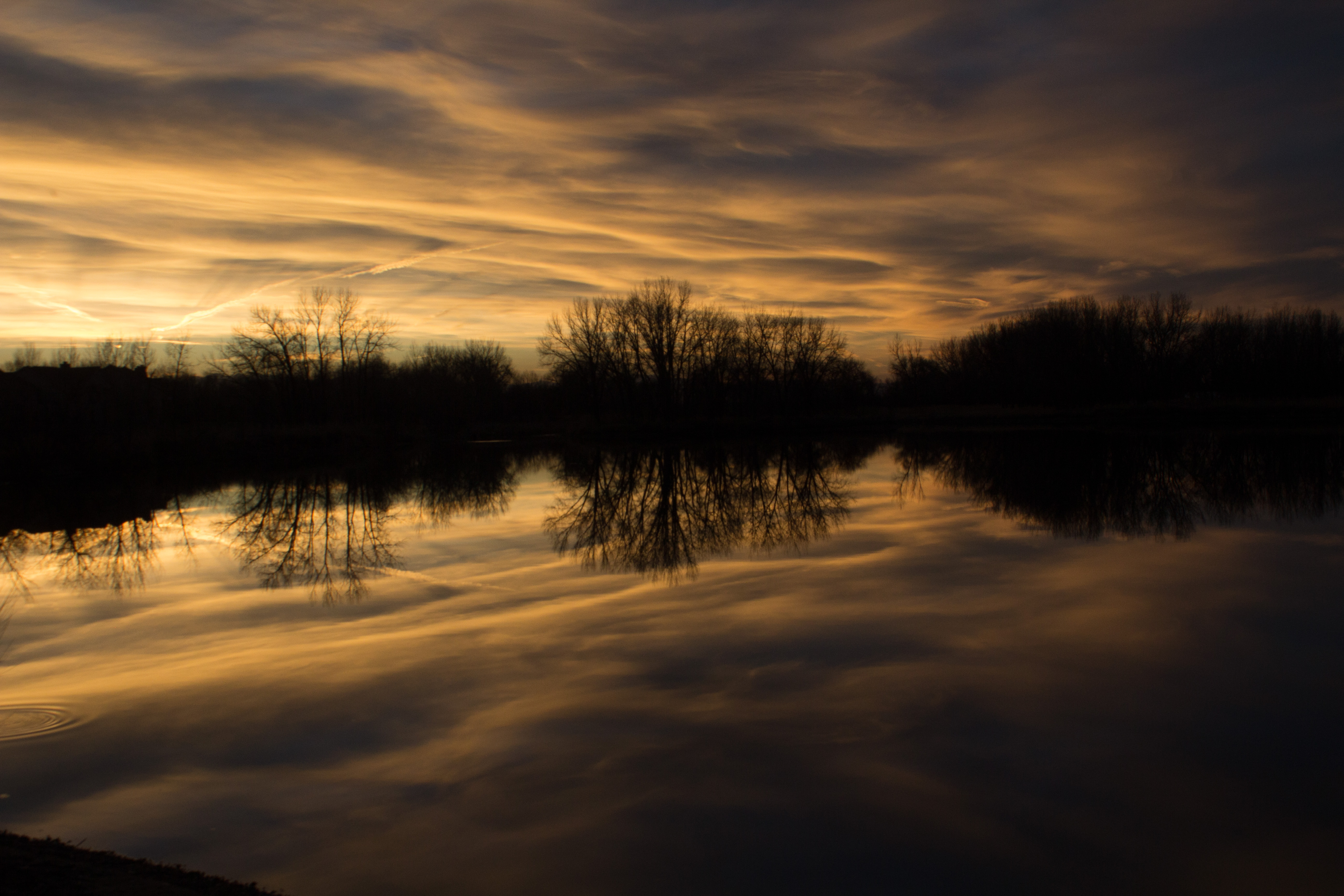 Sunset clouds reflected on still water