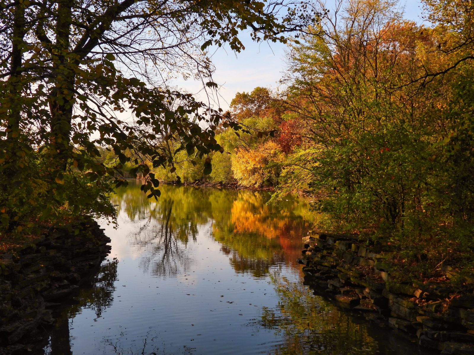 Looking Down River on Brisk October Day with Beautifully Colored Trees with Leaves in Orange, Yellow, Red and Green Reflected in Water with Bright Blue Sky in Background