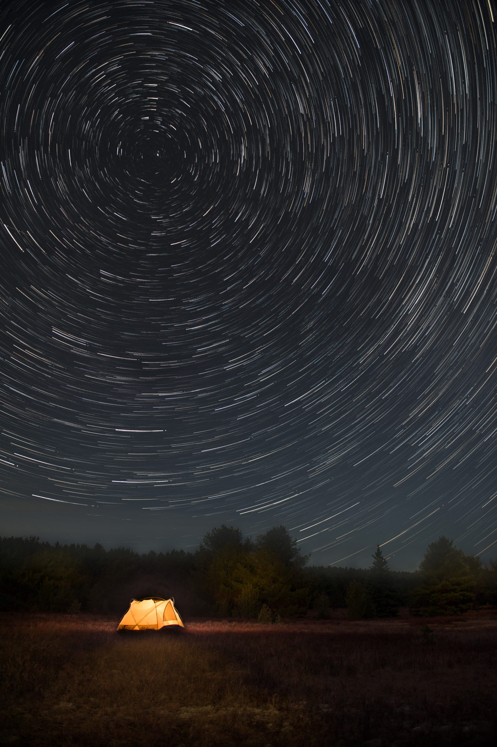 Star Trails Over a Glowing Tent