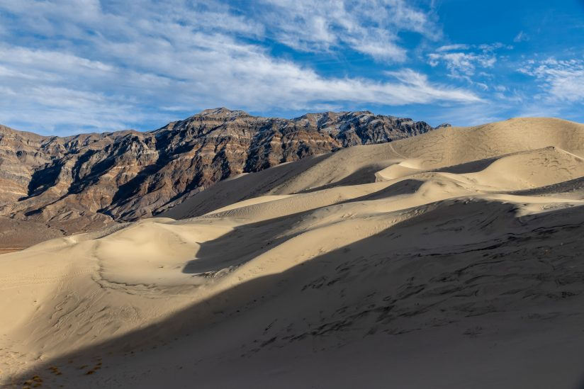 Sand Dunes, Mountains And Sky